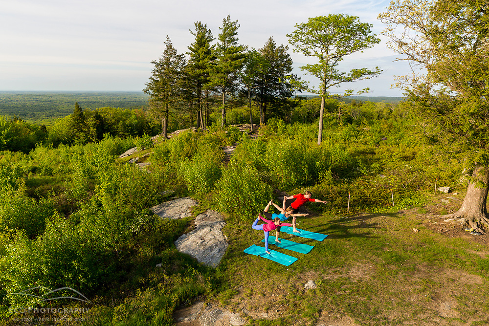 A woman and her teenage son and daughter do yoga on the summit of Mount Agamenticus in York, Maine.