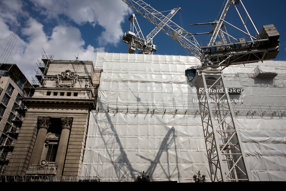 Shadow of a large crane on white sheeting covering City of London construction project.