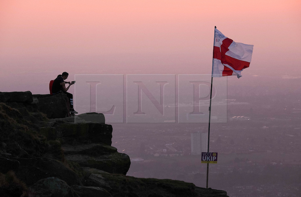 © Licensed to London News Pictures. <br /> 10/04/2015. <br /> Eston, United Kingdom<br /> <br /> Two men sit on a rocky outcrop next to a St George flag with a placard attached showing support for UKIP on the top of local landmark, Eston Nab on Teesside ahead of the General Election on May 7.<br /> <br /> Photo credit : Ian Forsyth/LNP