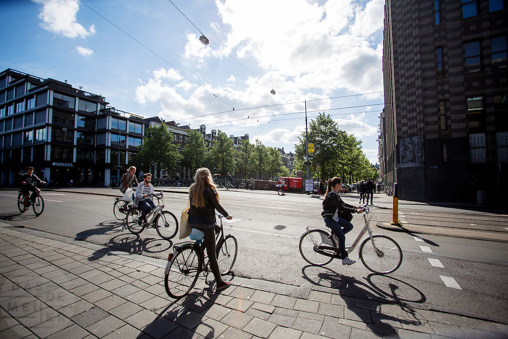 Fietsers kruisen elkaar bij de Vijzelstraat in Amsterdam. Twee toeristen rijden op een huurfiets.<br /> <br /> Cyclists crossing at the Vijzelstraat in Amsterdam. Two tourists ride on a rental bike.