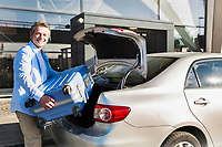 Portrait of mature businessman putting his luggage on car trunk with lens flare