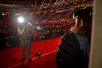 Graduate student poses for an official photo before crossing the stage for her diploma.