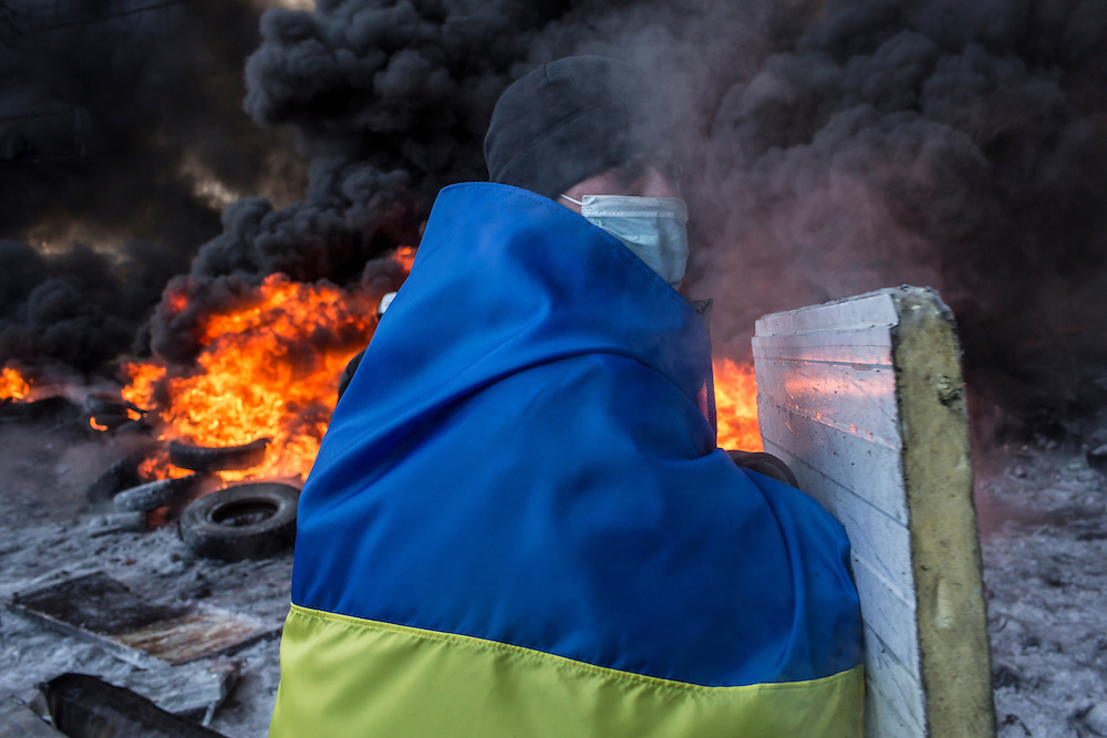 KIEV, UKRAINE - JANUARY 25: An anti-government protester wrapped in a Ukrainian flag watches as tires burn during clashes with police on Hrushevskoho Street near Dynamo stadium on January 25, 2014 in Kiev, Ukraine. After two months of primarily peaceful anti-government protests in the city center, new laws meant to end the protest movement have sparked violent clashes in recent days. (Photo by Brendan Hoffman/Getty Images) *** Local Caption ***