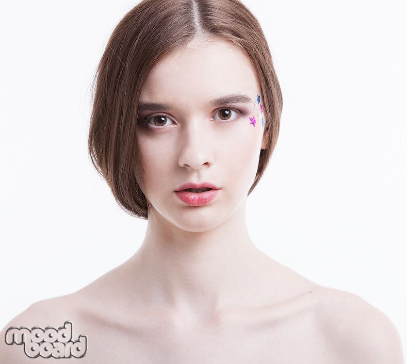 Portrait of beautiful young woman with stars on her face against white background