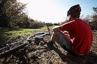 Mountain biker sitting beside bike in countryside
