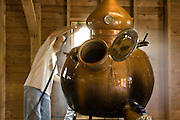 Keith Bodine cleaning a pot still at Sweetgrass Winery, Union Maine. The still is a variation of an ancient alembic still, once used by alchemists.