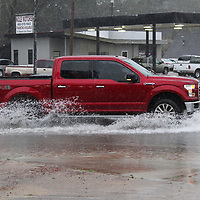 A Ford F150 goes through an area of road ponding at the intersection of Highway 278 and Main Street Wednesday morning.