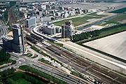 Nederland, Haarlemmermeer, Hoofddorp, 17-05-2002; omgeving van het NS Station (met intercity), kantorenpark Beukenhorst, midden rechts met bomen: doorgraven Liniedijk (onderdeel Hollandse Waterlinie / Stelling van Amsterdam); rechts van het spoor - betonnen lint naar horizon - vrije busbaan:  Zuid tangent; HSL trace begint bij het Station; kantoorflats nieuwbouw bowkranen infrastructuur, bouwen, spoor, rail, planologie ruimtelijke ordening<br /> luchtfoto (toeslag), aerial photo (additional fee)<br /> foto /photo Siebe Swart