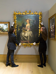 London, July 3rd 2017. Bonhams gallery staff straighten Thomas Hudson's Portrait of Albinia Bertie As A Young Girl, Seated in a Landscape holding a Basket of Doves, a Spaniel at Her Feet, which is expected to fetch £60-80,000 in their Old Master Paintings sale.