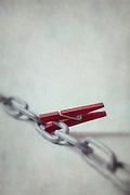 a red clothes-peg on a chain