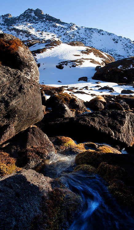 Alpine stream and rocky landscape covered with snow at Gosaikunda, a high altitude stop for trekkers, Nepal