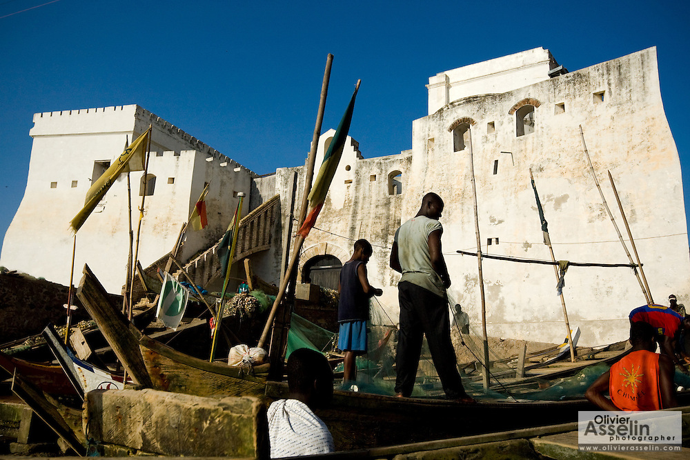 Fishermen stand on their boats while cleaning nets under the towering former slave fort of Cape Coast castle in Cape Coast, roughly 120km west of Ghana's capital Accra on Thursday April 9, 2009. Cape Coast's slave-trading days may be long gone but the town is no stranger to modern exploitation. Pirate fishing vessels and illegally-operating foreign trawlers are raping the seas, stealing the town's biggest commodity - its fish.