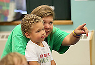 """Assistant Teacher Laura Fox (right) points out a picture to Quinton Garner, 3, of Cedar Rapids, as Pearson employees read """"Otis"""" by Loren Long to the class during Jumpstart's Read for the Record event at Waypoint Uptown Kids Child Development Center in Cedar Rapids on Thursday, October 3, 2013. Jumpstart's Read for the Record in partnership with the Pearson Foundation is a world-record-breaking campaign that brings together children and adults to read the same book on the same day. 73 Pearson employees from their Iowa City location visited 34 schools and daycares in Cedar Rapids, Iowa City, and the surrounding area as part of the program."""