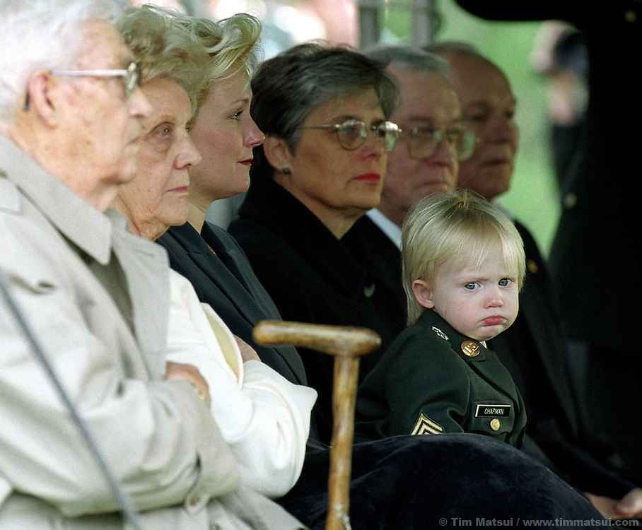 Brandon Chapman pouts on his mother Renae's lap during the burial ceremony for his father, Sgt. 1st Class Nathan Chapman, at the Tahoma National Cemetery in Kent, Washington, on Friday, January 1, 2002. Chapman was the first U.S. soldier to be killed by hostile fire in Afghanistan since ground troops were committed..