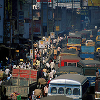 Crowds of people, advertising, and pollution-laden traffic jams on the approach to Howrah Bridge.