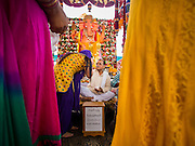 31 AUGUST 2014 - SARIKA, NAKHON NAYOK, THAILAND: Hindu priests bless women during the Ganesh Festival at Shri Utthayan Ganesha Temple in Sarika, Nakhon Nayok. Ganesh Chaturthi, also known as Vinayaka Chaturthi, is a Hindu festival dedicated to Lord Ganesh. It is a 10-day festival marking the birthday of Ganesh, who is widely worshiped for his auspicious beginnings. Ganesh is the patron of arts and sciences, the deity of intellect and wisdom -- identified by his elephant head. The holiday is celebrated for 10 days, in 2014, most Hindu temples will submerge their Ganesh shrines and deities on September 7. Wat Utthaya Ganesh in Nakhon Nayok province, is a Buddhist temple that venerates Ganesh, who is popular with Thai Buddhists. The temple draws both Buddhists and Hindus and celebrates the Ganesh holiday a week ahead of most other places.    PHOTO BY JACK KURTZ