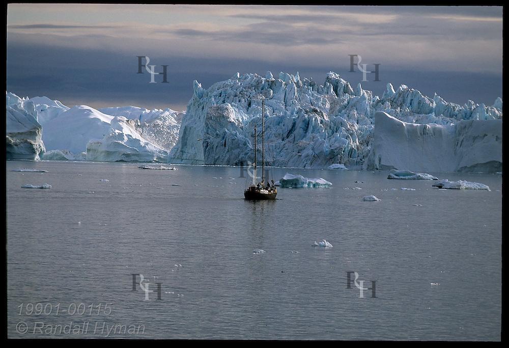 Icebergs calved from Sermeq Kujalleq glacier clog Disko Bay where Ilulissat Kangerlua Icefjord meets sea, dwarfing boat; Greenland