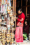 A monk buys new prayer beads from a stall opposite the Boudhanath stupa in Kathmandu, Nepal.