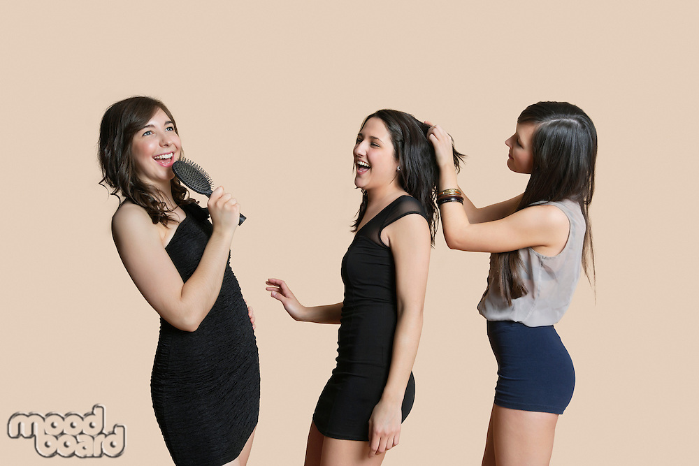 Cheerful young females enjoying together over colored background