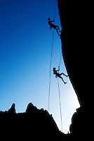 Silhouettes of a man and a woman as they rappel a rock face.