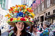 New York, NY - April 16, 2017. A woman wears a straw hat topped with dozens of tulips at New York's annual Easter Bonnet Parade and Festival on Fifth Avenue.
