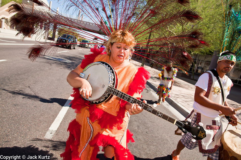 "10 OCTOBER 2010 - PHOENIX, AZ:  A woman plays a banjo while she performs with a Matachine group in Phoenix, AZ, Sunday. About 500 people processed through downtown Phoenix Sunday afternoon to honor the Virgin of Guadalupe, the ""Queen of the Americas."" The procession was accompanied by 12 Matachine dance troupes. The Matachines are an important part of Mexican Catholic culture. They represent the battle of Good vs. Evil and the protect the Virgin from malevolent forces, represented by the demon like figures who accompany the dancers.      Photo by Jack Kurtz"