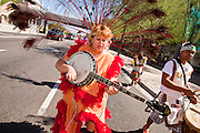 """10 OCTOBER 2010 - PHOENIX, AZ:  A woman plays a banjo while she performs with a Matachine group in Phoenix, AZ, Sunday. About 500 people processed through downtown Phoenix Sunday afternoon to honor the Virgin of Guadalupe, the """"Queen of the Americas."""" The procession was accompanied by 12 Matachine dance troupes. The Matachines are an important part of Mexican Catholic culture. They represent the battle of Good vs. Evil and the protect the Virgin from malevolent forces, represented by the demon like figures who accompany the dancers.      Photo by Jack Kurtz"""