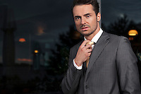 Portrait of angry businessman adjusting necktie in office
