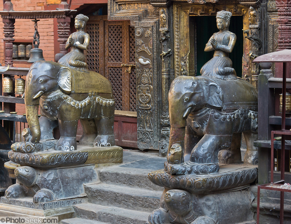 """Sculptures of armored elephants carry Buddhas on turtle bases at Golden Temple (Hiranya Varna, or Suwarna Mahavihara), a Buddhist Monastery existing since 1409 or earlier, located just north of Patan's Durbar Square, in Nepal, Asia. Patan was probably founded by King Veer Deva in 299 AD from a much older settlement. Patan, officially called Lalitpur, the oldest city in the Kathmandu Valley, is separated from Kathmandu and Bhaktapur by rivers. Patan (population 190,000 in 2006) is the fourth largest city of Nepal, after Kathmandu, Biratnagar and Pokhara. The Newar people, the earliest known natives of the Kathmandu Valley, call Patan by the name """"Yala""""  (from King Yalamber) in their Nepal Bhasa language. UNESCO honored Patan's Durbar Square (Palace Square) as one of the seven monument zones of Kathmandu Valley on their World Heritage List in 1979. All sites are protected under Nepal's Monuments Preservation Act of 1956."""