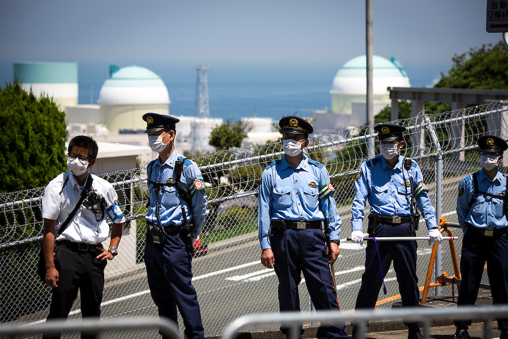 EHIME, JAPAN - AUGUST 11 : Police officers guard the gate from anti-nuclear protesters who gather in front of Ikata Nuclear Power Plant to protest against the restarting of a nuclear reactor on August 11, 2016 in Ikata, Ehime prefecture, northwestern Shikoku, Japan. The No. 3 reactor of the nuclear plant is expected to resume operations this week after The Nuclear Regulation Authority (NRA's) has completed it's final inspections of the plant's operational safety measures. The plant has not generated nuclear power since Japan's 2011 nationwide shutdown of all nuclear plants in the aftermath of the Fukushima Daiichi nuclear disaster. Ikata Nuclear Power Plant will be the third nuclear power plant in Japan to become operational. (Photo by Richard Atrero de Guzman/NURPhoto)