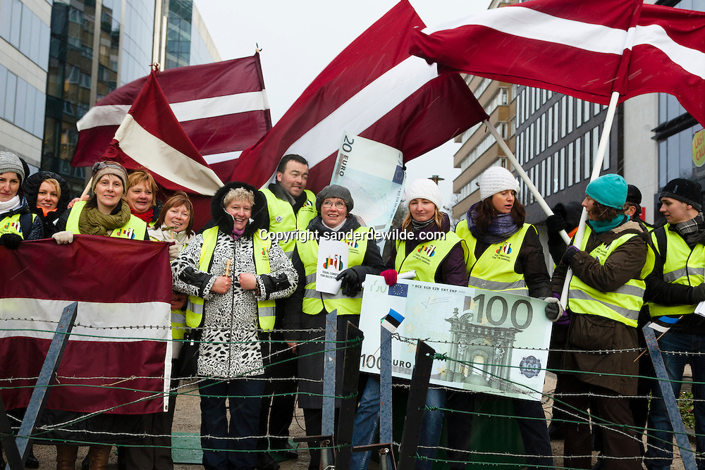 Brussels 7th February 2013. Ahead of  EU budget talks in Brussels, over 100 farmers from the Baltics gathered in Schuman Square demanding fairer direct payments..The farmers are in good spirits, singing songs and armed with posters, and are holding the Latvian, Lithuanian and Estonian flags.Protesters wave 110 euro money and the Latvian flag