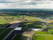 Nederland, Noord-Holland, Gemeente Schermer, 16-04-2012; in de voorgrond Polder K (rechts) en Polder L, onderdeel van de Schermer, droogmakerij met blokverkaveling. Op het tweede plan het dorpje Driehuizen met rechts daarvan en er achter de Eilandspolder (laagveen gebied, vaarpolder of vaarland). Aan de horizon de geometrische verkaveling van de Beemster, in de verre achtergrond het IJsselmeer..Nice examples of land division in North-West Netherlands. Bottom picture square fields of the land division of the polder Schermer, right (next to the central village) a polder created by peat  extraction, at the horizon the regular geometric land divison of the polder Beemster..luchtfoto (toeslag), aerial photo (additional fee required);.copyright foto/photo Siebe Swart