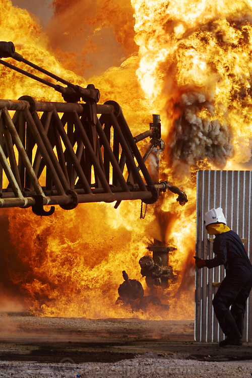 "Two Kuwaiti Oil Company firefighters shelter themselves from the intense heat of an oil well fire in a spray of water, behind a piece of metal roofing as they guide a ""stinger"" on the end of a long boom that will pump drilling mud into the gushing well at high pressure to stop the fire and flow of gas and oil. Rumaila oilfield, southern Iraq. The Rumaila field is one of Iraq's biggest with 5 billion barrels in reserve. Many of the wells are 10,000 feet deep and produce huge volumes of oil and gas under tremendous pressure, which makes capping them very difficult and dangerous. Rumaila is also spelled Rumeilah."
