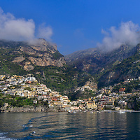 The village of Positano surrounded by hills and mountains of the Amalfi Coast in southern Italy in this breathtaking panorama taken from the sea.