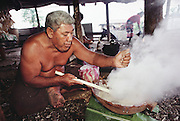 Auseuga Lagavale, the matai (head) of his extended family, is cooking his favorite coconut sauce, in preparation for a feast at the Lagavale home in Western Samoa. The recipe: wring out fresh coconut meat with the fibers from the husk, boil juice in a bowl by droping in rocks heated by fire, dribble in sugar, stir constantly until the milky white sauce thickens. He is cooking in the family's detached cooking shed behind the main house. Published in Material World, page 172.