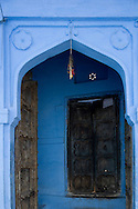 A wooden door at a traditional blue painted house in Jodhpur, Rajasthan, India