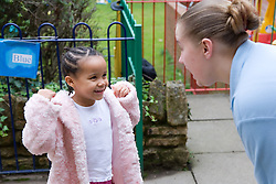 Little girl talking to playschool care assistant,