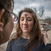 "ALEXANDRIA, VA - MAR1: Pastor Robin Anderson, from  Commonwealth Baptist church, puts ""glitter ashes"" on Chaaron Pearson, for Ash Wednesday, outside the Braddock Road metro station, in Alexandria, VA, March 1, 2017. Across the country, churches involved with the advocacy group Parity will be giving out ""glitter ashes"" to demonstrate that LGBT people should be included in Christianity.(Photo by Evelyn Hockstein/For The Washington Post)"