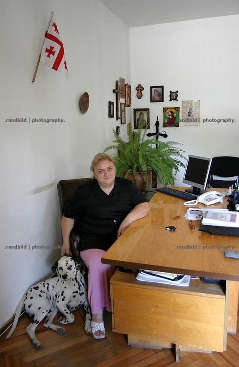 Mediko Alanja, Direktorin des einzigen georgischen Frauengefaengnises in Tiflis, sitzt an ihrem Schreibtisch zwischen Natinalfahne und Religion. Mediko Alanja, Director of Woman Prison of Tbilissi, Georgia.