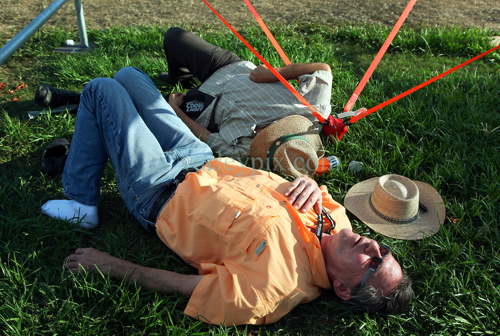 30 April 2015. New Orleans, Louisiana.<br /> The New Orleans Jazz and Heritage Festival. <br /> A couple get to sleep off their early hangovers.<br /> Photo; Charlie Varley/varleypix.com