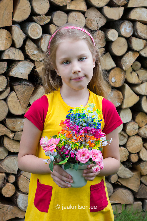 Young caucasian girl holding candy tree. Piled and stacked firewood in Estonia