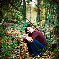 A young girl sitting in the woods looking at the camera