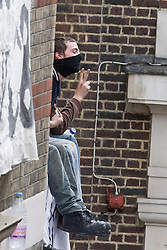 © Licensed to London News Pictures . 11/06/2013 . London , UK . One of those in the building gestures . Police surround a former police station on 40 Beak Street , Soho this morning (11th June) . The site has been occupied by organisers of today's Stop G8 anti capitalist protests . Demonstrations in London today (Tuesday 11th June 2013) ahead of Britain hosting the 39th G8 summit on 17th/18th June at the Lough Erne Resort , County Fermanagh , Northern Ireland , next week . Photo credit : Joel Goodman/LNP