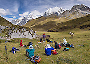 Trekkers lunch in Yanayana Valley below Siula Grande and Yerupaja Grande (center 6635 m / 21,770 ft, Peru's 2nd highest peak). Day 2 of 9 days trekking around the Cordillera Huayhuash in the Andes Mountains, Peru, South America. This panorama was stitched from 5 overlapping photos.