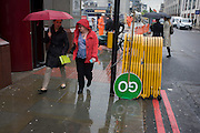 Commuters and upside down GO construction traffic sign in a busy London rush-hour street.