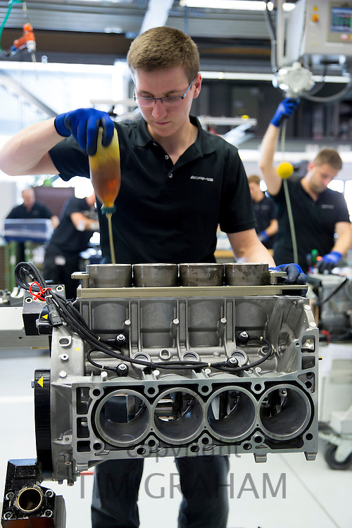 Mercedes-AMG engine production factory in Affalterbach, Germany - engineer applies lubricant oil into cylinders for pistons of 6.3 litre V8 engine