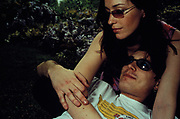 Couple wearing sunglasses, cuddling in Regents Park, London, U.K 2000.
