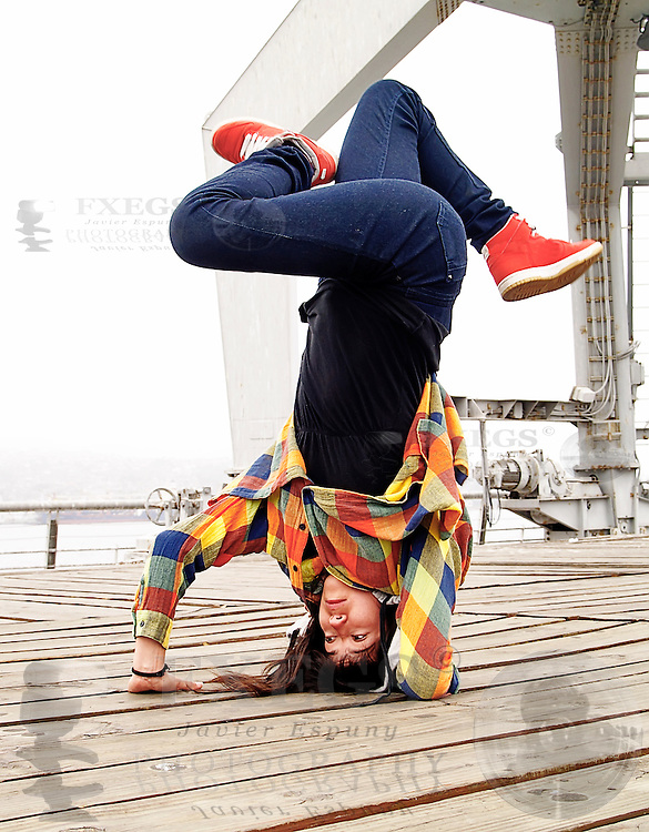 Young female breakdancing in a handstand pose