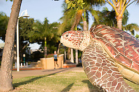 A jogger exercises on The Strand under the watchful gaze of a Loggerhead Turtle statue.