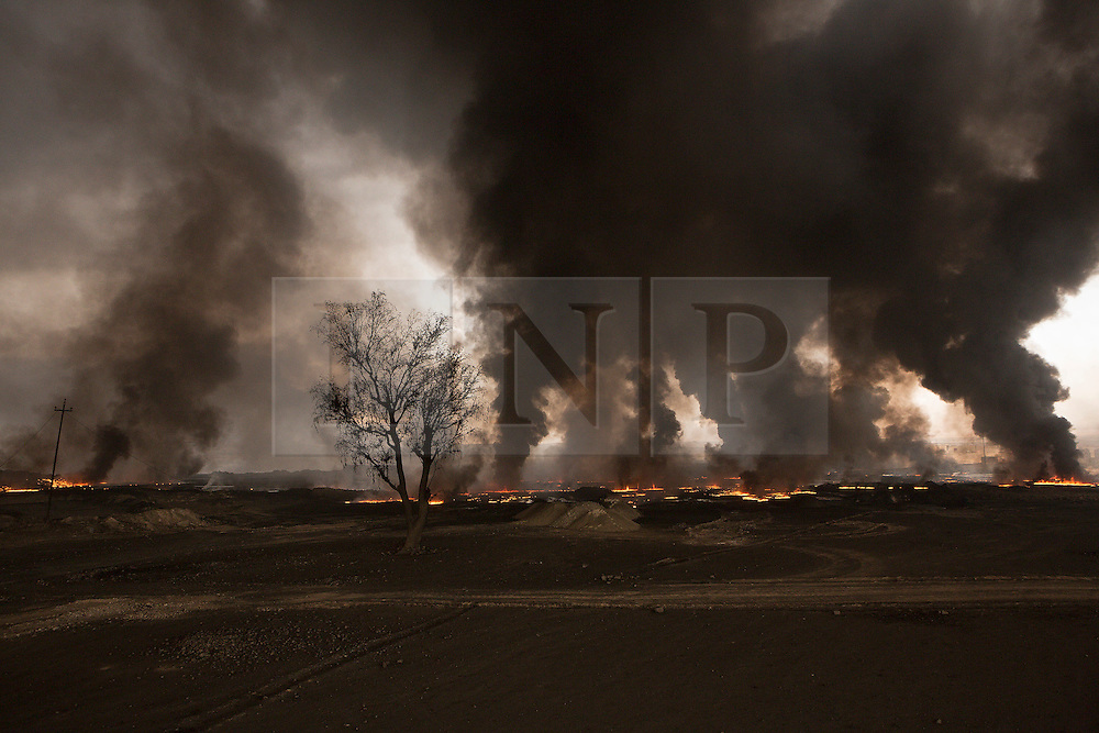Licensed to London News Pictures. 08/11/2016. Qayyarah, Iraq. Flames and smoke rise from a burning oil facility in the town of Qayyarah, Iraq. Oil wells in and around the town of Qayyarah, Iraq, we set alight in July 2016 by Islamic State extremists as the Iraqi military began an offensive to liberated the town.<br /> <br /> For two months the residents of the town have lived under an almost constant smoke cloud, the only respite coming when the wind changes. Those in the town, despite having been freed from ISIS occupation, now live with little power, a water supply tainted with oil that only comes on periodically and an oppressive cloud of smoke that coats everything with thick soot. Many complain of respiratory problems, but the long term health implications for the men, women and children living in the town have yet to be seen. Photo credit: Matt Cetti-Roberts/LNP